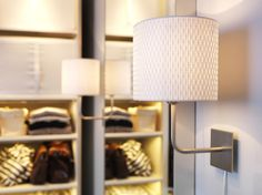 Two ALÄNG wall lamps on either side of a bedroom mirror cast a flattering light.