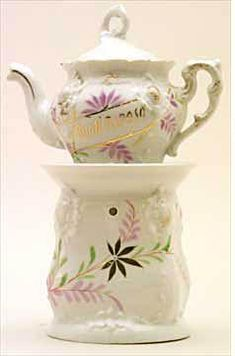 """Teapot #470  Dainty pot with unusual handle and finial, with """"Buon Riposo"""" in Italian on pot; both pot and   base have white background with lavender flowers surrounded by gold sprays"""