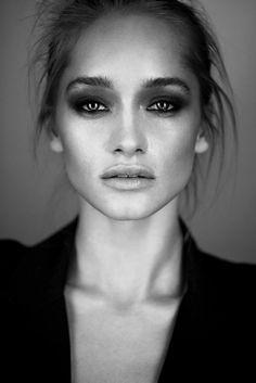 portrait noir et blanc du visage d'une femme avec les yeux maquillés avec effet fumé, lèvres pulpeuses, cheveux pris dans une queue de cheval décontractée