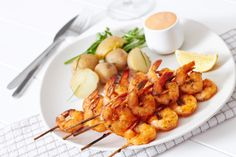 Shrimps skewers with potatoes and scampi sauce