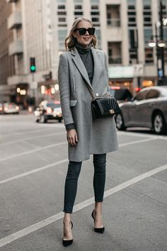 548d62c9109 Blonde Woman Wearing Grey Coat Grey Turtleneck Sweater Grey Skinny Jeans  Black Pumps Black Chanel Boy
