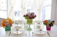 canvas potted bouquets including orange lilies tulips poms on a table with Easter eggs plates and silverware and lemonade in glass soda bottles in front of window