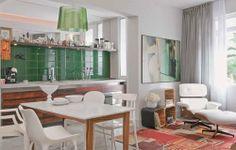 Neste apartamento de 57 m², cozinha e sala é uma coisa só. As áreas são diferenciadas pelas cores marcantes, como o verde escuro do azulejo da cozinha. O contraste fica por conta do tapete da sala, em tons quentes.
