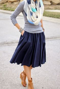 Cute and simple look. Long sleeved gray T, navy midi pleated skirt, neutral sandals, and oversized neutral scarf with colors to bring outfit together.