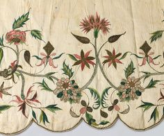 Detail, apron, probably England, c. 1725-1750. Cream silk taffeta, hand embroidered with a Jacobean floral pattern with polychrome silk floss and bronze metallic floss. The scalloped edges arte trimmed with corded floss.