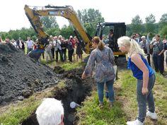 Begraven van het 'bouwoffer'. Het komt onder de drempel van de ingang van het Archeologisch Informatiecentrum