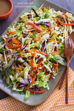 Colorful Asian cole slaw is dressed with almond butter dressing with ginger, garlic and sesame. Make it ahead, toss with dressing when ready to serve