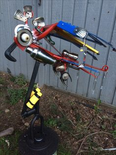 "This sculpture is called ""Lost Shaker of Salt"" a  parrot manufactured out of repurposed metal, plastic, bike parts bar accessories and golf balls for eyes!  It is designed to turn into the wind for improved stability.  The perfect piece of colorful yard are for any Margaritaville fan"