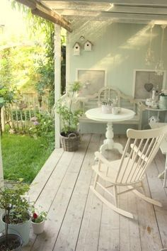Old porch painted pale green - love the white rocking chair