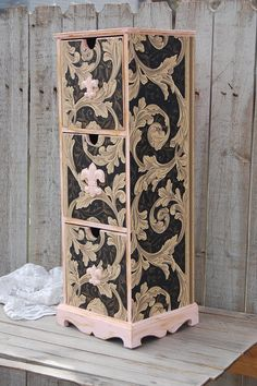 Versatile upcycled vintage cabinet. Wood, hand painted in soft pink with wood Fleur de Lis shaped appliques also painted pink, lightly accented in gold and decoupaged in a gold and black leaf pattern
