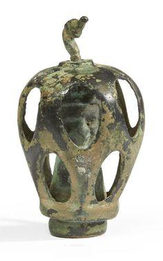 ORNEMENT À TÊTE HUMAINE. Élément d'ornementation formé d'une coque ajourée renfermant une figurine représentant une tête masculine, les cheveux coiffés en mèches horizontales parallèles. L'ensemble est maintenu, au sommet, par un crochet en tête de canard. Bronze. Luristan, début du Ier millénaire av. J.-C. H_9 cm