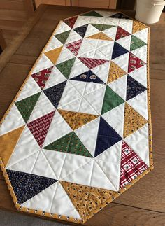 Quilted table runner. The runner is made with quality Moda fabric from American Jane (Lorraine) This item is machine pieced and quilted. The backing can be seen in photo #3. Binding is hand sewn. Machine washable. Dimensions: 17.5 by 40.25 Made from cotton print fabrics and