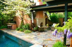 Love the step into the pool.  Fireplace with covered patio (nicely keeps the heat in) Nice green everywhere Stone, Outdoor Kitchen, Fence, Pathway, Traditional, French, Lap Pool