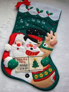 """This wonderful hand~crafted Christmas Stocking called """"DECK THE HALLS""""  is made of felt applique on cloth and beautifully decorated with hand sewn sequins and beads. Santa, Frosty and Rudolph ane singing Deck the Halls. Portions of this stocking are stuffed creating a 3-dimensional appearance. There is room at the top to have a special name embroidered. Heirloom Quality!  This measures approx. 21"""" diagonally and 10"""" across the top."""
