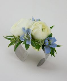 A dazzling corsage featuring two ranunculus blooms, accented with light blue delphinium.