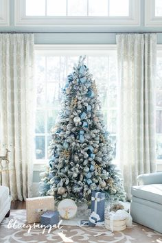 flocked christmas tree with frontgate ornaments with presents under the tree by large windows in a sun room
