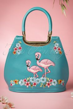 This 50s Flamingo Handbag in Blue by Banned is a beautiful, elegant bag with a colourful embroidery.This spacious bag is made from a sturdy, nice quality faux leather in light teal and is a real eyecatcher with its floral, flamingo embroidment! The golden details and short straps give the bag a lovely chique glow. It's also very sensible because of the space and some additional pockets on the inside. There's a zipper to close the bag and it comes with a lose adjustab...