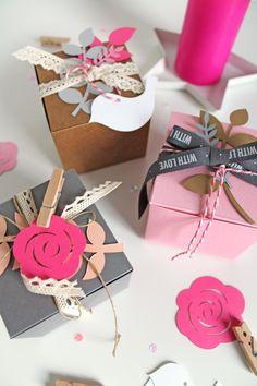 Utiliza elementos troquelados y cógelos con pinzas a las cintas que cierran el regalo para decorar