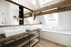 Opting for an unfinished plank of #timber, the #rustic #vanity in this fantastic #bathroom is paired with sleek #contemporary finishes that really make it stand out from the crowd. Image by Buero Philipp Moeller. Need help with your #home? Consult #homify! #design #moderndesign #interior #moderninterior #interiordesign #modernliving #modernbathroom #rusticbathroom #wood #wooden #beams #woodenbeams #bathtub #skylight #slopedceiling #attic #undertheroof