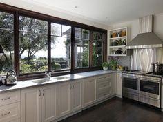 farmhouse kitchen- sink under windows- dark sashes, white walls