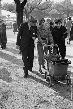 Mother and father both wearing nationalist uniforms take their baby for a ride in her pram accompanied by grandma in San Sebastian which is controlled by the fascists.