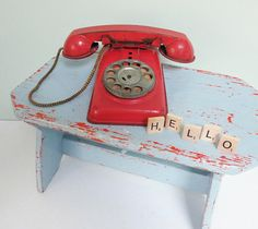 I just love this vintage toy telephone! It would be fun to display this playful relic in a home office, on your desk at work or in a childs room.  This pretend phone is made out of metal with muted red paint on its body. A red metal receiver is attached with a fabric cord and it sports the