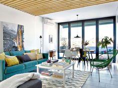 Un apartament spațios unde tonurile vesele de culoare se îmbină armonios cu detaliile din lemn de pe tavan și pereți