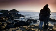 Couple standing on the Giant's Causeway watching the sunset