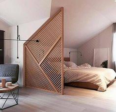 Un claustra en bois sépare le coin nuit dans un studio