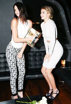 Kendall Jenner wears a black and white tank, printed trousers, and heels, Gigi Hadid wears a white crop top, pencil skirt, and strappy sandals