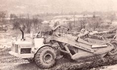 In New Castle Pennsylvania, one of Bracken Construction's early Allis-Chalmers 460Bs gets a load of wet and heavy material on the Route 422 bypass. The conditions are fairly cold and miserable so the operator has placed a sheet of cardboard across the entranceway to the cab to retain some heat given off by the engine!