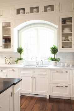 Hendel Homes: Dreamy kitchen with topiaries flanking kitchen sink. Kitchen sink alcove with floor to ...