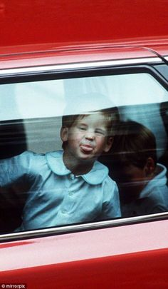 Harry, aged three, sticks his tongue out at waiting photographers in the backseat of a car...