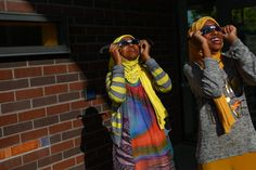 Young people use protective eyewear to watch the sun during a solar eclipse viewing party at the High Point Branch of the Seattle Public Library.