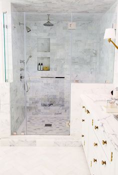 Bathroom with grey marble shower, glass shower doors, marble counter tops, white drawers with brass details, white tile floor, and white and gold lights