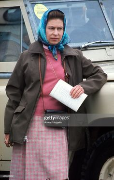 Queen Elizabeth ll, wearing a headscarf and carrying a camera, relaxes during Badminton Horse Trials on April 18, 1975 in Badminton, England.