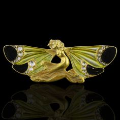 Exquisite Art Nouveau brooch designed as a crouching nymph in 18ct yellow gold her arms as outstretched wings with light green plique-à-jour, and dark green cloisonné enamel and rose-cut diamond highlights René Lalique, Paris circa 1898