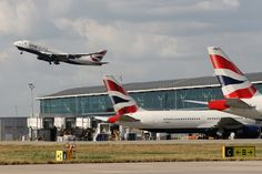 British Airways Boeing 747 in oneworld livery takes off from London Heathrow with a few BA tailfins and Terminal 5.