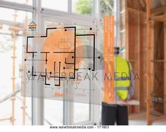 Architect looking out window with house plans in foreground Image by Wavebreak Media