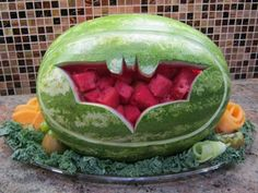 Batman carved watermelon. Maybe make the hole bigger and make as a fruit bowl with cantaloupe, honey dew, grapes, etc.