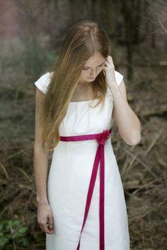 schlichtes, bodenlanges hochzeitskleid in empirelinie, rock leicht ausgestellt mit kleiner schleppe, seidenband unter der brust in pink mit pinker blume aus seidenorganza (Foto: Hanna Witte) (http://www.noni-mode.de)