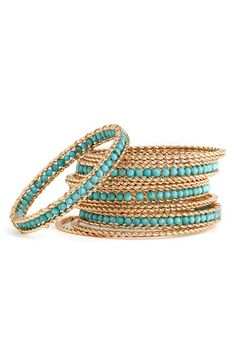 Stack of bangles in twisted gold & turquoise beads