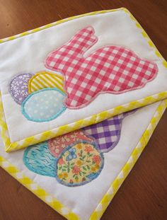This set of two mug rugs or snack mats is perfect for enjoying a special Easter treat! These versatile little mats feature cute gingham bunnies and pastel Easter eggs on a fresh and simple white field. Each mat is made from different coloured fabrics that coordinate together beautifully, and are backed and bound with yellow gingham. The bias binding has been bound by hand to the mat back. The bunnies and eggs are machine-appliqued using a satin stitch with coordinating thread. The mats…