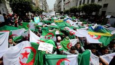 """Anti-government protests in Algiers, Algeria, with a banner reading """"Government go away – students take over,"""" April 2019. President Abdelaziz Bouteflika bowed to pressure from the military and weeks of popular protests by stepping down from power. The protestors are continuing to call for the removal and prosecution of what they see as corrupt and ineffective elites who have collectively ruled Algeria since independence from France in 1962.  Photo credit: Ramzi Boudina — in Algiers…"""