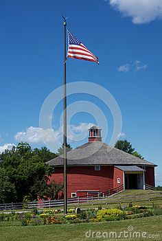 This is a front view of the main entrance of a historic round barn at Shelburne Museum in Shelburne Vermont. At the entrance is a flower garden and an American flag Shelburne Vermont, Shelburne Museum, Cool Countries, Countries Of The World, Main Entrance, Barns, Museums, American Flag, United States
