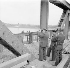 BRITISH ARMY NORTH-WEST EUROPE 1944-45 PRIME MINISTER CROSSES RHINE (BU 2258) Prime Minister, Field Marshal Montgomery and General Simpson, on blown bridge at Wesel. Town in background. While on bridge enemy were shelling river.