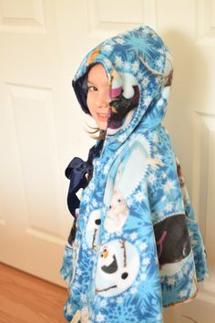 Get a warm hug with this snugly cape has purple Frozen fleece with Elsa and Anna on one side and navy polka dot minky on the other. It has an