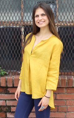 Pascal Top by CP Shades  Pull over linen tunic top in marigold color. Round split neckline  & pleat 3/4 sleeve to roll or not. Side seam pockets. Hi lo hemline. Back yoke with center pleat.