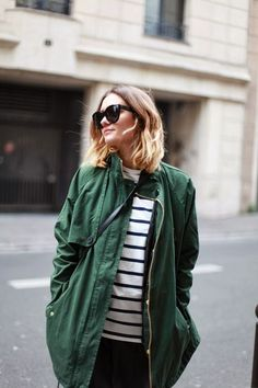 Dark green parka style jacket, worn over a striped crossbody | Image via bloglovin.com