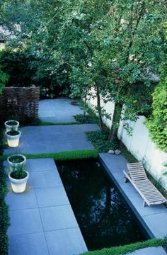 small, urban, contemporary garden. Salix, willow, woven wall, Hedera, ivy, Thymus serpyllum, creeping thyme, water feature, terrace, ground cover plants, teak, wooden furniture, big grey freestone tiles, pavement, flooring, container, flowerpot 'Bloom', overview   Design: Kristof van den Bouwhuysen
